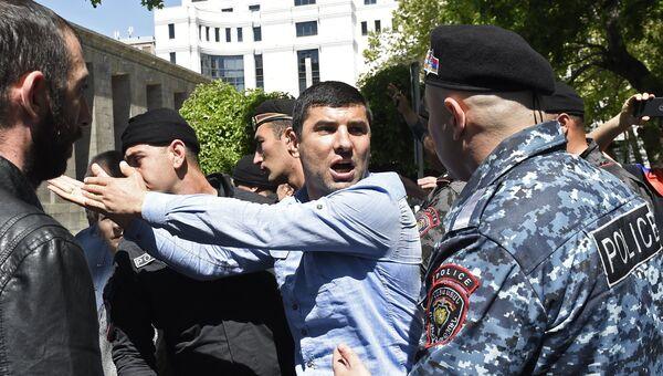 Мужчина и сотрудник правоохранительных органов на улице в Ереване. 25 апреля 2018