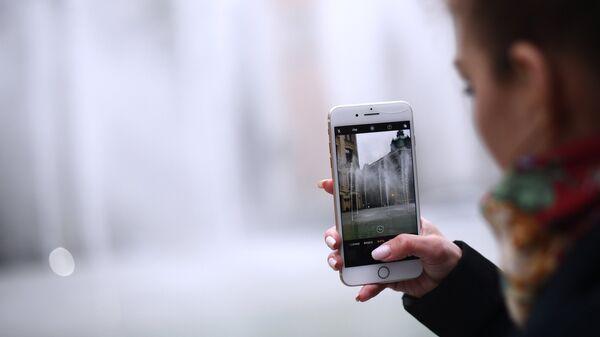 Девушка фотографирует фонтан. Архивное фото