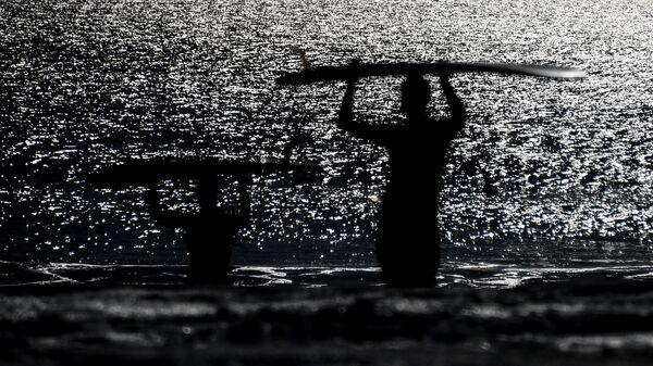 Серферы заходят в воду