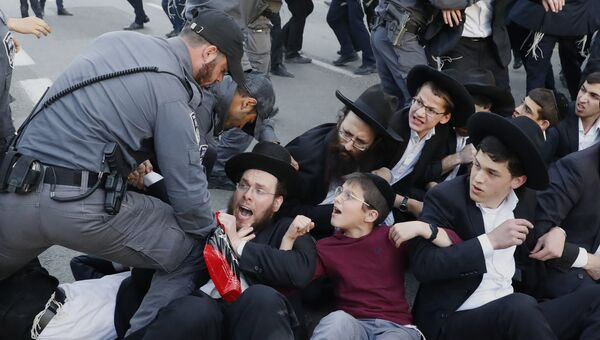 Сотрудники израильской службы безопасности пытаются разогнать ультраортодоксальных евреев во время демонстрации против воинского призыва в городе Бней-Брак, Израиль