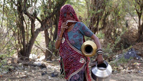 Женщина набирает питьевую воду из придорожной колонки на окраине Аджмера, в индийском штате Раджастхан. Архивное фото
