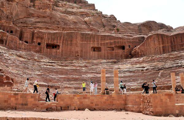 Туристы осматривают амфитеатр, построенный древними набатейцами, в городе Петра в Иордании
