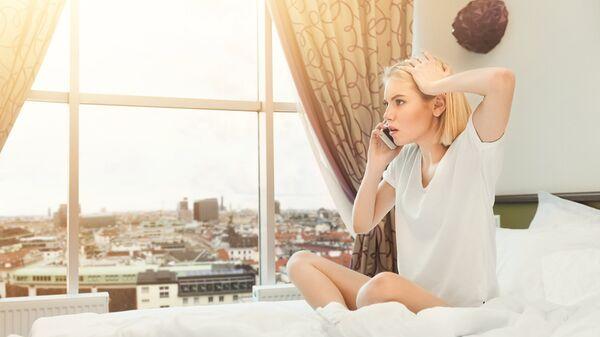 Девушка разговаривает по телефону в гостиничном номере