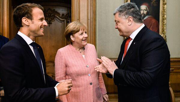 Президент Франции Эммануэль Макрон, канцлер Германии Ангела Меркель и президент Украины Петр Порошенко во время встречи в городе Аахен в Германии. 10 мая 2018