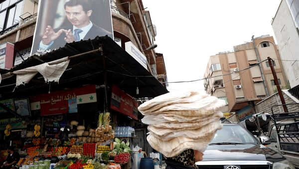Женщина несет стопки хлеба на голове в Дамаске, Сирия. 10 мая 2018