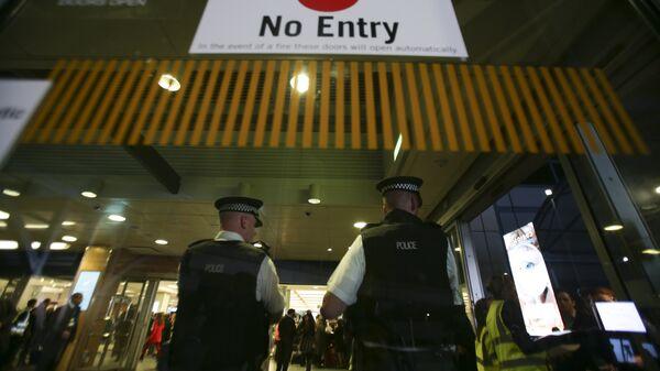Сотрудники британской полиции у входа в терминал аэропорта в Лондоне. Архивное фото