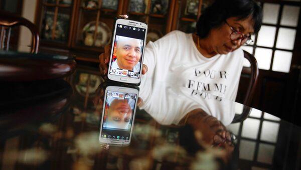 Портрет пилота пропавшего самолета Boeing 777-200 авиакомпании Malaysia Airlines Захарии Ахмада Шаха на экране телефона