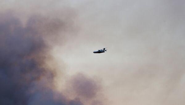 Самолет МЧС РФ тушит пожар над территорией бывшего военного арсенала в поселке Пугачево в Удмуртии. 17 мая 2018
