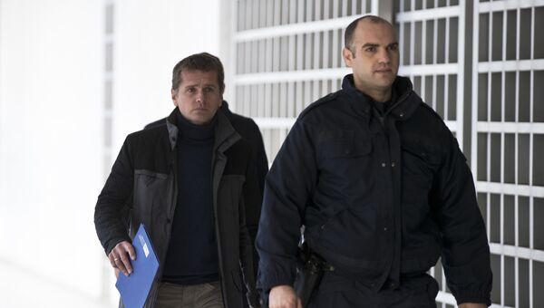Полицейский сопровождает Александра Винника в Верховный суд Греции в Афинах. Архивное фото