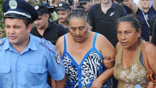 Сотрудники правоохранительных органов успокаивают жителей села Лощиновка в Одесской области, где произошли столкновения и погромы домов цыган