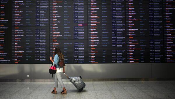 Пассажир у табло в аэропорту. Архивное фото