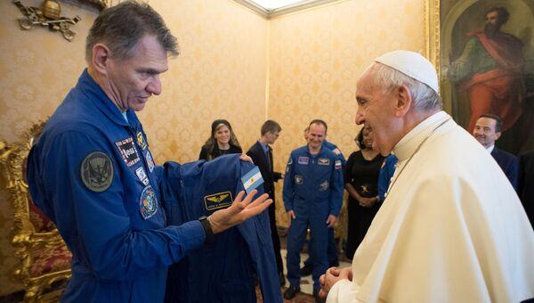 Астронавт Поало Несполи вручает костюм космонавта МКС Папе Римскому Франциску. 8 июня 2018
