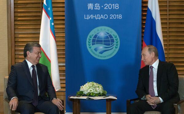 Владимир Путин и президент Республики Узбекистан Шавкат Мирзиёев во время встречи на полях саммита ШОС. 9 июня 2018