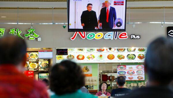 Трансляция встречи президента США Дональда Трампа и лидера КНДР Ким Чен Ына в торговом центре в Лос-Анджелесе, США. 12 июня 2018