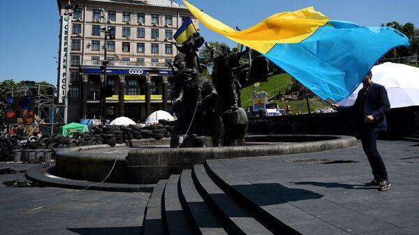Молодой человек с украинским флагом у памятника основателям Киева на площади Независимости