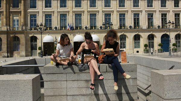 Туристы обедают на Вандомской площади в Париже.