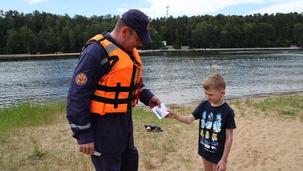 Спасатель первого класса Сергей Картавый вручает информационную листовку маленькому Диме. На пляж мальчик пришел с мамой