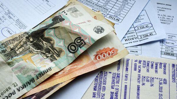 Денежные купюры и квитанции за оплату коммунальных услуг. Архивное фото