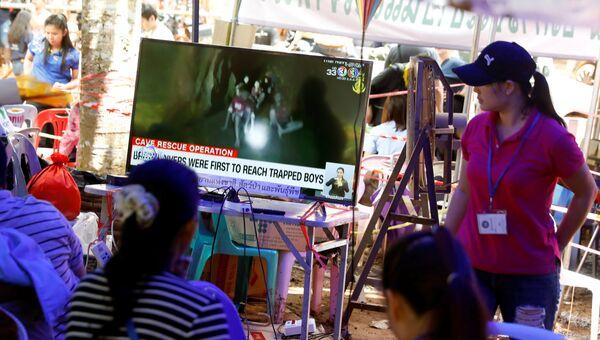 Члены семьи смотрят трансляцию из пещеры Тхам Луанг, где находятся мальчики и тренер. 4 июля 2018 года