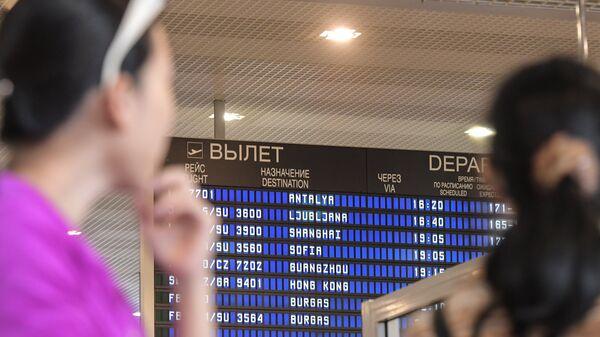 Пассажиры у информационного табло аэропорта