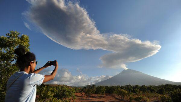 Девушка фотографирует столб дыма, выброшенный из вулкана Агунг в Индонезии