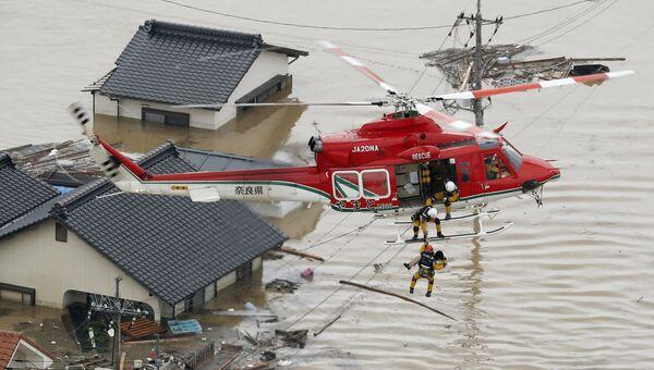 Cпасатели эвакуируют местного жителя из затопленного дома на юге Японии. 7 июля 2018