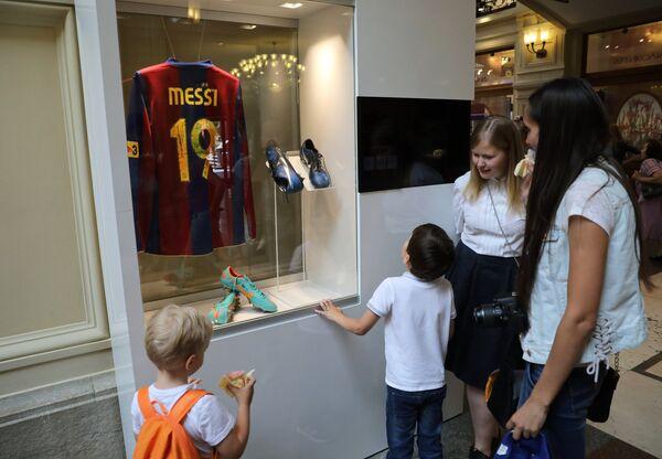 Посетители возле витрины с формой и бутсами футболиста сборной команды Аргентины Лионеля Месси, представленные на выставке футбольной атрибутики Qatar @RoadTo2022 Exhibition в ГУМе в Москве