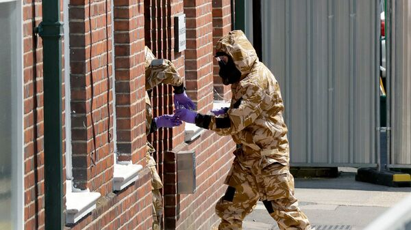 Сотрудники британских спецслужб в защитных костюмах у жилого дома в Солсбери