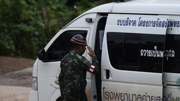 Тайская военная полиция приветствует машину скорой помощи, покидающую пещерную зону пещер Тхам Луанг. 10 июля 2018