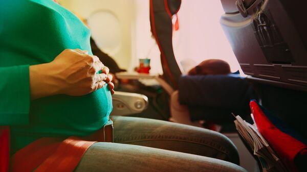 Беременная женщина в салоне самолета