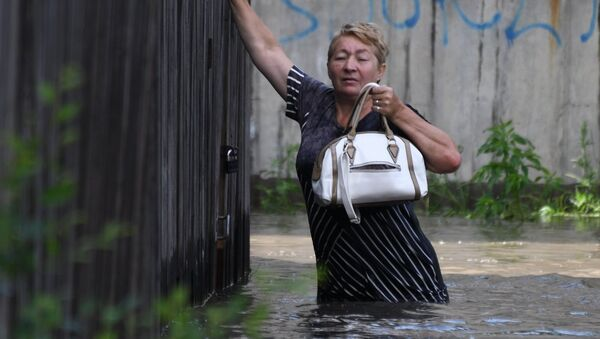 Местная жительница на улице Лазо в Чите, затопленной в результате притока воды в реке Читинка. 10 июля 2018