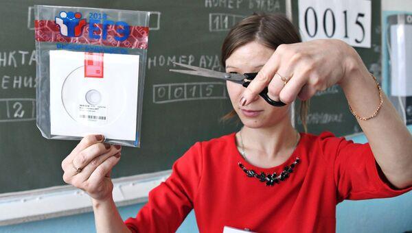 Учитель вскрывает пакет с диском, на котором содержатся задания для ЕГЭ по информатике и ИКТ в 2018 году