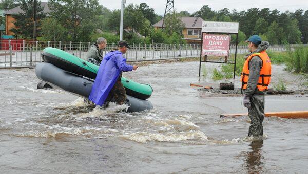 Сотрудники МЧС на затопленной в результате паводка улице в Чите. 11 июля 2018