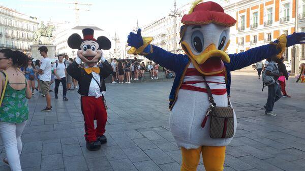 Люди в костюмах Микки Мауса и Дональд Дака на площади в Мадриде
