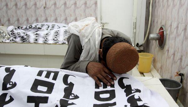 Мужчина скорбит над телом члена его семьи, который погиб в результате взрыва бомбы в городе Кветта провинции Белуджистан в Пакистане. 13 июля 2018