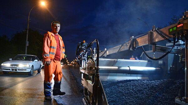 Рабочий во время укладки асфальта по приоритетному проекту Безопасные и качественные дороги на улице Немировича-Данченко  в Новосибирске. 20 июля 2018