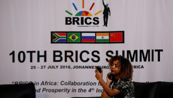 Девушка на фоне логотипа саммита BRICS-2018