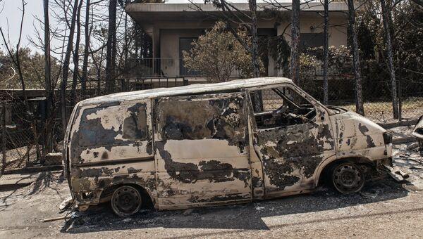 Сгоревший в результате лесных пожаров автомобиль на улице Мати в Греции. Архивное фото