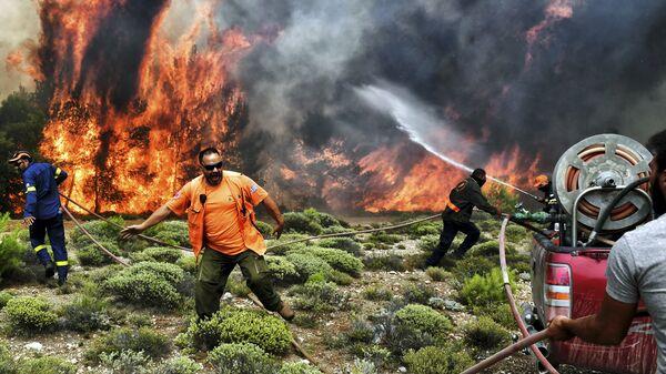 Пожарные и волонтеры пытаются потушить лесной пожар в деревне Кинета, недалеко от Афин. 24 июля 2018 года