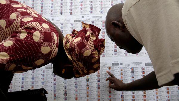 Люди ищут свои имена в списке избирателей в Бамако. Архивное фото