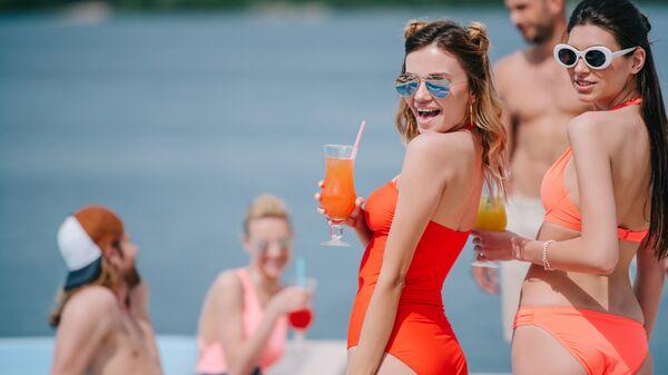 Девушки с коктейлями на пляже