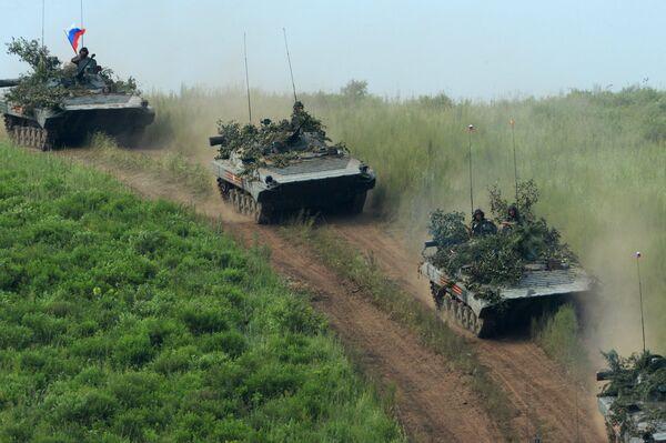 БМП-2 совершают марш перед преодолением водной преграды по понтонному мосту во время показных учений в Приморском крае.