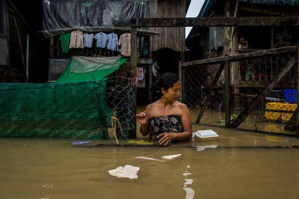 Девушка на улице города Баго во время наводнения в Мьянме.