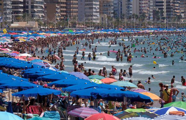 Люди на пляже в городе Бенидорм, Испания.