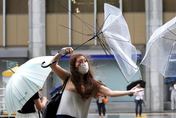 Девушка с зонтом во время приближения тайфуна Шаньшань в Токио. 8 августа 2018 года