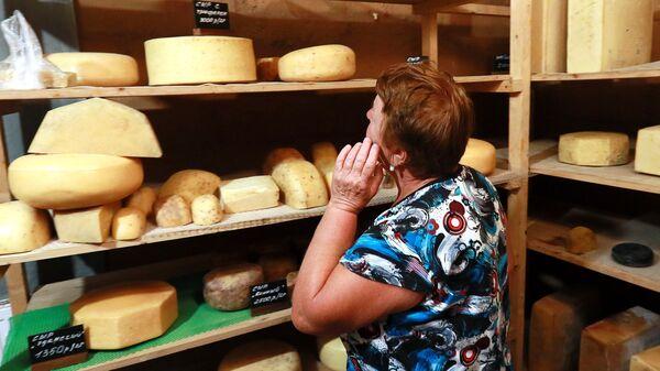 Покупательница выбирает сырную продукцию фермера Джея Роберта Клоуза в магазине при ферме в Московской области, деревни Мошницы