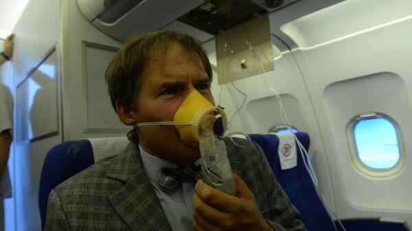 Пассажир в кислородной маске во время учений по отработке нештатных ситуаций на борту