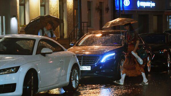 Прохожие на улице Москвы во время дождя. Архивное фото