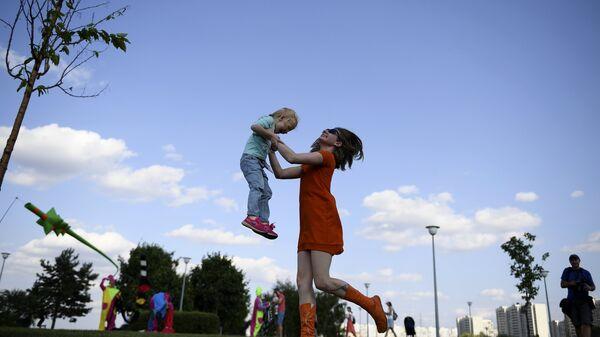 Женщина с ребенком в Братеевском каскадном парке Москвы, где проходит фестиваль фейерверков Ростех