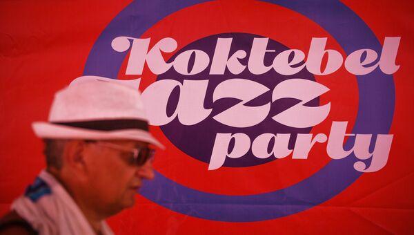 Прохожий у информационного баннера Международного джазового фестиваля Koktebel Jazz Party в Крыму